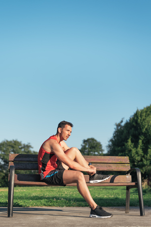 Sportsman resting and tying his running shoes during outdoor cross training workout. Fit fitness sport male model sitting on a bench outside using street furniture.
