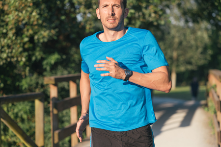 Male runner running in urban park close up.  Strong man athlete exercising outdoor.