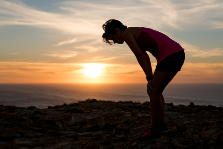 Side view of a exhausted and tired woman silhouette at sunset after running workout taking a rest Banco de Imagens - 65878265