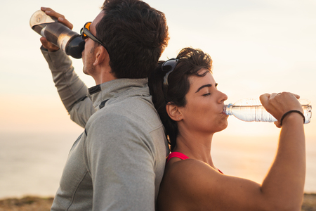 Sporty couple drinking water afer outdoor workout. Fitness healthy hydration concept.