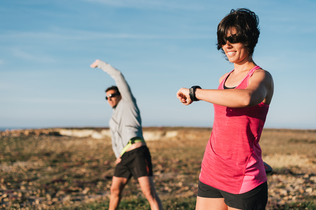 Couple runners warming up before trail running workout. Woman looking at watch before exercising outside. Stock Photo