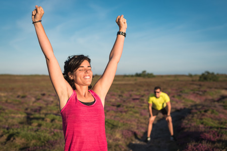 Smiling runner woman rising her arms after wining trail running training race. Couple competitively while preparing marathon or triathlon competition.