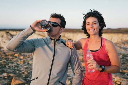 Fitness sport running couple resting and drinking water outside smiling after exercise workout Banco de Imagens