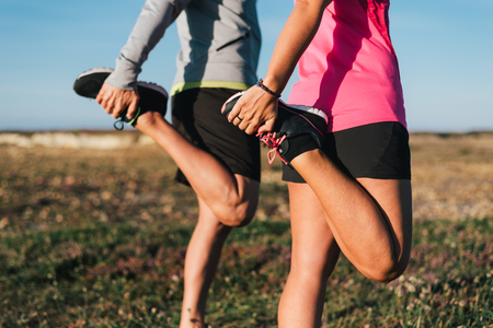 Sporty couple stretching legs outdoors before trail running workout outdoors. Fitness healthy lifestyle concept. Banco de Imagens