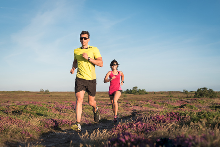 Sporty couple running outdoor cross country. Woman and man doing cardioexercise workout.