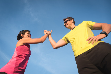 Fit sport running couple celebrating cheerful and happy giving high five. Smiling sporty people after winning competition.