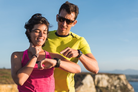 Fitness runner woman smiling and checking heart rate pulse with watch and trainer pointing during outdoor trail running workout. Couple team doing sport outside together training for a marathon or decathlon competition. Banco de Imagens