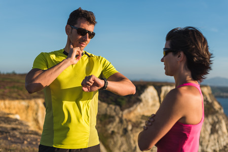 Fitness fit runner man smiling and checking heart rate pulse with watch and trainer during outdoor trail running workout. Couple team doing sport outside together training for a marathon or decathlon competition.