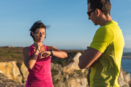 Fitness runner woman checking heart rate pulse with watch and trainer during outdoor trail running workout. Couple team doing intensity workout outside together training for a marathon or decathlon competition. Banco de Imagens