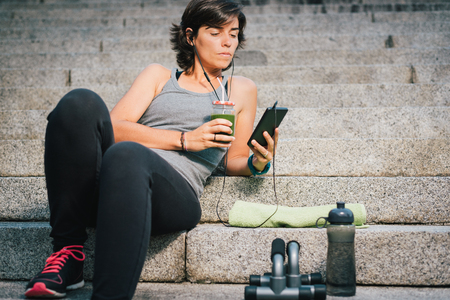 Woman drinking juice vegetable green detox cleanse smoothie after fitness running workout listening music using her phone with bottle of water and towel. Healthy lifestyle concept.