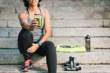 cleanse: woman showing juice vegetable green detox cleanse smoothie after fitness running workout with phone, bottle of water and towel. Healthy lifestyle concept. Stock Photo