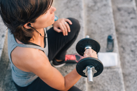 fitness woman lifting weight training arms with dumbbell outside on urban stone stairs with towel, earphones and bottle of water during exercises workout routine. Sporty Female wellness concept. Banco de Imagens