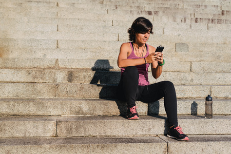 Fitness sporty woman listening to music and using chat app on phone while resting during an outdoor training workout with a bottle of water sitting on stone stairs.