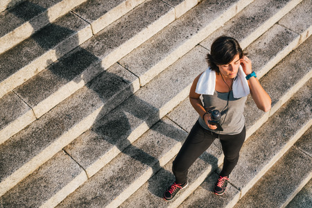 Fitness sporty runner woman listening to music on phone holding cell and bottle of water closing eyes enjoying sunlight for motivation before training workout routine