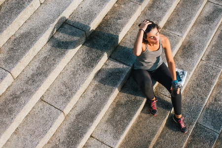 Runner sitting resting after urban running routine. Woman athlete relaxing enjoying sun and drink from water bottle after exercising outdoor in sunshine with phone, earphones and towel.
