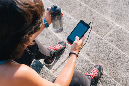 Athlete woman sitting on stone stairs resting and listening music on smart phone with bottle of water while resting from outdoors urban training exercise workout. Female wellness concept.