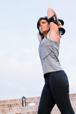 Sport woman lifting weight training arms with dumbbell outside on urban stone stairs with towel, earphones and bottle of water during exercises workout routine. Female wellness concept.