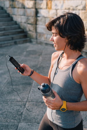 Sportswoman standing resting and listening music on smart phone holding bottle of water while resting from outisde urban training exercise workout. Female wellness concept.