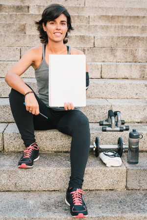 Fitness sporty woman showing blank notepad while sitting on urban stone stairs during exercises workout routine. Female athlete trainer focusing on goals.