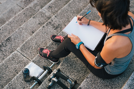 Fitness sporty woman writing on blank notepad while sitting on urban stone stairs before exercises workout routine. Female athlete focusing on her goals.