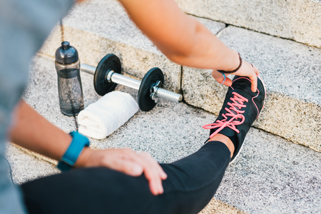 Sport athlete runner female stretching leg on urban stone stairs during training exercise workout routine with bottle of water, towel and dumbbell. Fitness woman outdoor routine.