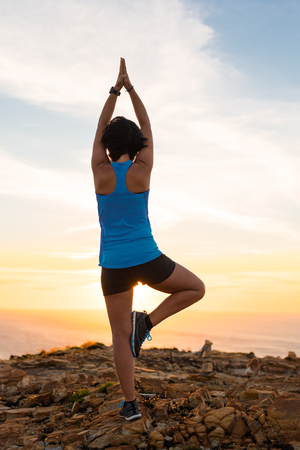 Fitness woman doing yoga exercises outdoor at the coastline for balance sport workout with blue t-shirt at sunset Banco de Imagens