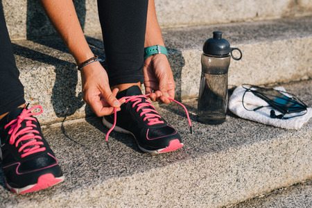 Woman tying pink laces of sport shoes closeup sitting on outdoors stairs with towel, bottle of water and phone with earphones before running training workout routine.