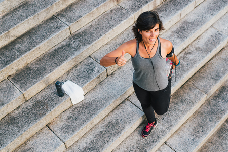 Fitness sporty runner woman listening to music with earphones with bottle of water and towel  for motivation before training workout routine smiling and giving thumbs up and stretching legs.