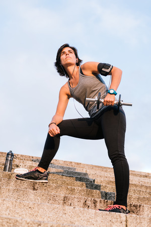 Sport woman lifting weight training with dumbbell outside on urban stone stairs with towel, earphones and bottle of water during exercises workout routine. Female wellness concept.
