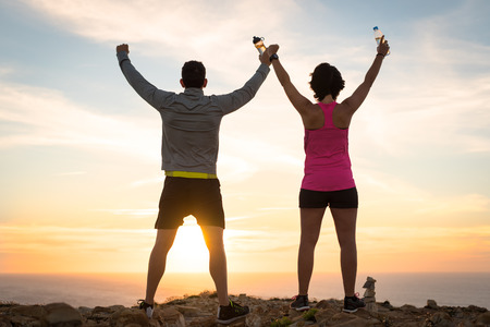 Sporty runner couple rising arms in victory sign after successful training outdoor on the coast facing the sun showing back. Running team success concept.