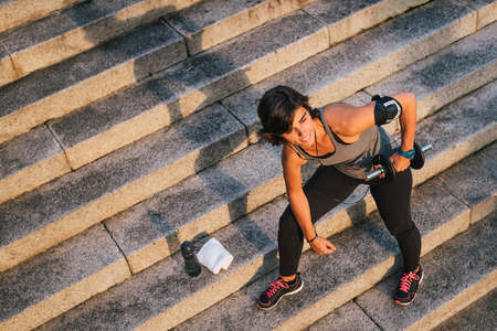 Sport woman lifting weight training with dumbbell outside on urban stone stairs with towel and bottle of water during exercises workout routine. Female wellness concept.