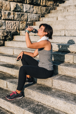 Runner drinking water after urban running routine. Woman athlete resting enjoying sun and drink from water bottle after exercising outdoor in sunshine holding phone and towel. Banco de Imagens