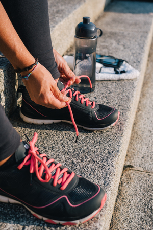 Woman tying pink laces of sport running shoes closeup sitting on outdoors stairs with towel, bottle of water and phone with earphones before running training workout routine. Banco de Imagens