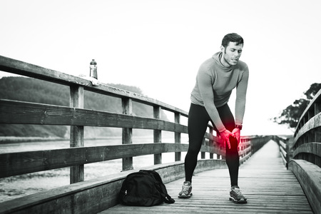 Fit runner sportsman holding knee in pain in a park. Broken twisted joint running sport injury. Athletic man touching leg due to sprain. Rodiles, Asturias. Banco de Imagens