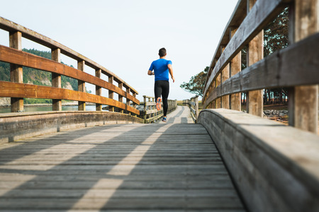 man running in park on wooden walkway training and exercising for trail run marathon race. Fitness healthy lifestyle concept with male athlete outdoor runner.