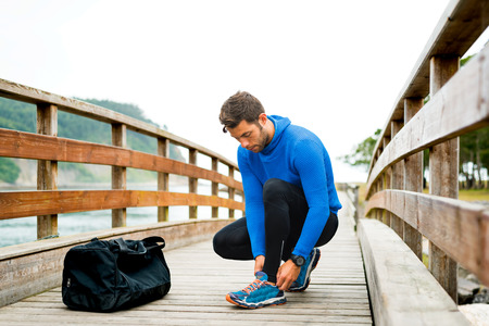 cloudy day: Strong sportsman adjusting tights and shoes for an outdoor running training on a cloudy autumn day with a sport bag on a wooden walkway. Fitness sporty man in Rodiles, Asturias. Stock Photo