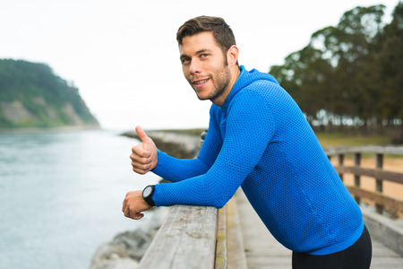 Smiling happy runner man resting during outdoor training workout giving thumbs up. Fit fitness sport model leaning on wooden railing for motivation at riverside park in Rodiles, Asturias.