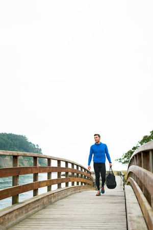Strong sportsman arriving at his outdoor training spot on a cloudy autumn day with a sport bag on a wooden walkway. Fitness sporty man in Rodiles, Asturias.