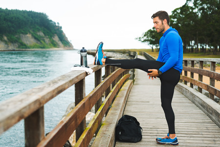 Fit sports man doing stretches before an outdoor running training on a cloudy autumn day with a sport bag on a wooden walkway. Fitness sporty man in Rodiles, Asturias.