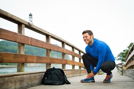Fit deportista corredor que sostiene el tobillo en el dolor en un parque. lesión deportiva conjunta funcionamiento trenzado rota. Atlético hombre de sus pies tocando debido al esguince. Foto de archivo