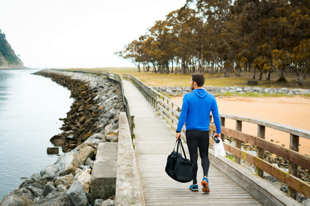 Strong sportsman leaving his outdoor training spot on a cloudy autumn day with a sport bag on a wooden walkway. Fitness sporty man in Rodiles, Asturias.