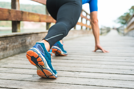 Fitness man ready for running on wooden walkway on an outdoor park. Male athlete in powerful confident starting line pose in Rodiles, Asturias. Sport Shoe sole closeup.