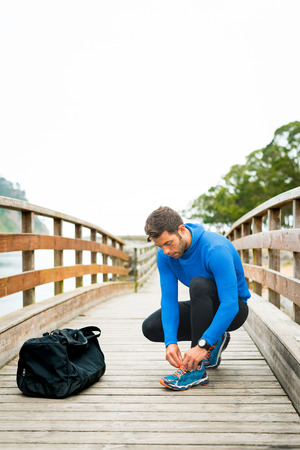 Strong sportsman adjusting tights and shoes for an outdoor running training on a cloudy autumn day with a sport bag on a wooden walkway. Fitness sporty man in Rodiles, Asturias. Banco de Imagens