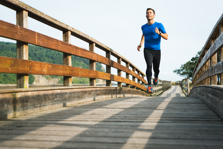 Smiling man running in park on wooden walkway training and exercising for trail run marathon race. Fitness healthy lifestyle concept with male athlete outdoor runner.