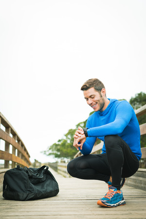 Strong smiling sportsman adjusting sport watch for an outdoor running training on a cloudy autumn day with a sport bag on a wooden walkway. Fitness sporty man in Rodiles, Asturias.
