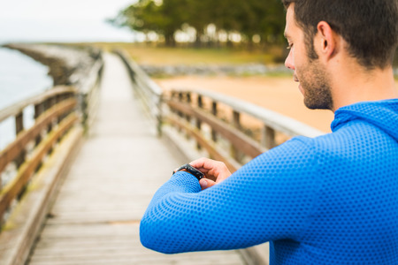 Strong smiling sportsman adjusting sport watch for an outdoor running training on a cloudy autumn day on a wooden walkway. Fitness sporty man in Rodiles, Asturias. Banco de Imagens