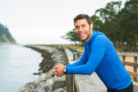Smiling happy runner man resting during outdoor training workout. Fit fitness sport model leaning on wooden railing for motivation at riverside park in Rodiles, Asturias.