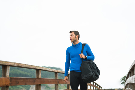 Strong runner man arriving at his outdoor training spot on a cloudy autumn day with a sport bag. Fitness sporty male in Rodiles, Asturias.
