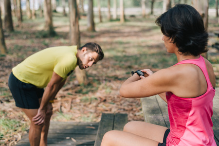 Sports coach woman trainer checking watch counter while her disciple is resting outdoor on a forest. Sporty couple exercising runner strength workout during a pause break. Stock Photo