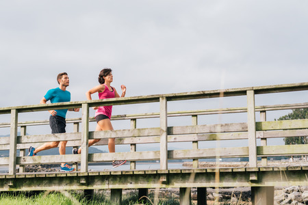 Couple doing running exercises workout training outdoor. Young caucasian runner couple  jogging outside on beautiful country scene. Fitness healthy lifestyle.